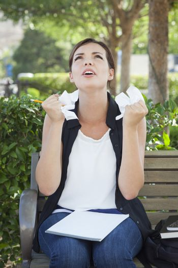 Frustrated and Upset Young Woman with Pencil and Crumpled Paper in Her Hands Sitting on Bench Outside.