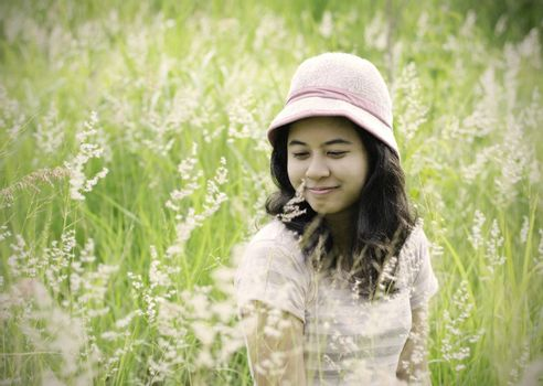 Young brunette woman on the meadow with white flowers on a warm summer day