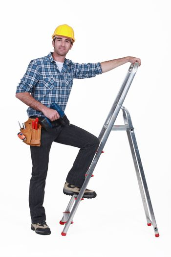 Man with drill climbing ladder