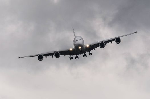 Airliner approaching for landing, cloudy sky