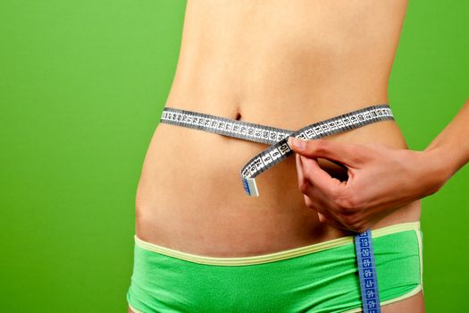 young woman measuring her slim body on green background