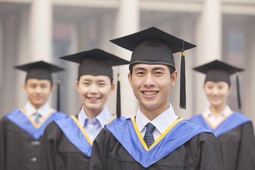 Four University Graduates Smiling, Looking at Camera