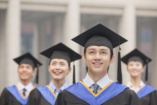 Four University Graduates Smiling, Looking Up