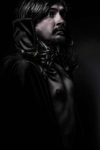 Elegant Young Vampire with black coat and long hair, nude