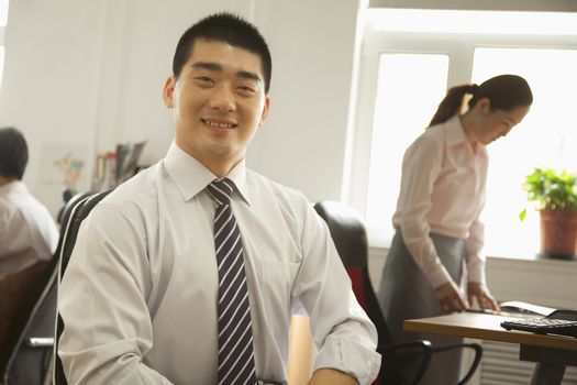 Office worker seating and smiling, portrait