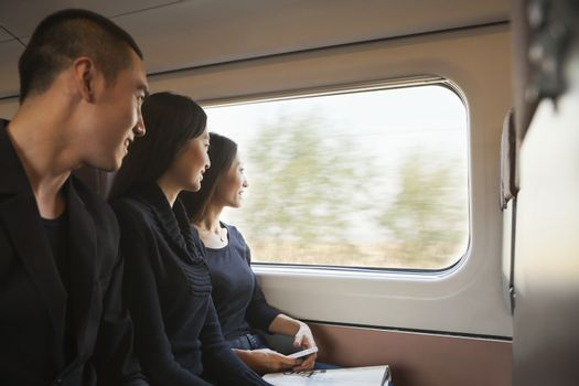 Three Friends Looking Out Train Window