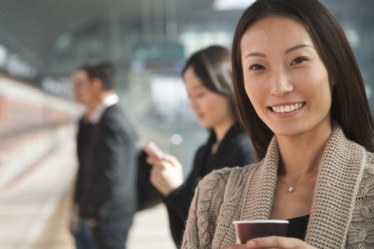 Young Woman Waiting on Train Platform with Coffee