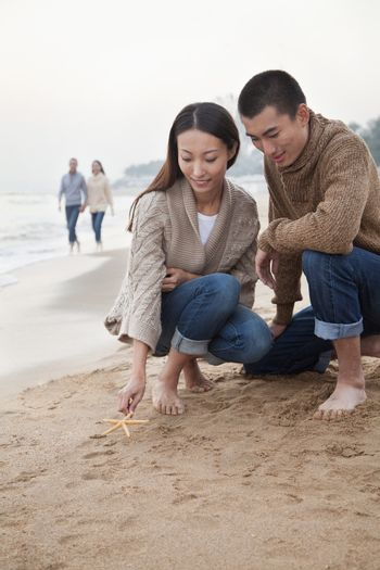 Young Couple Picking Up Starfish on the Beach