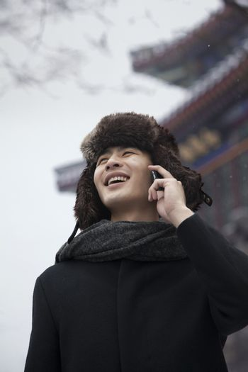 Man in Fur Hat Talking on Cell Phone