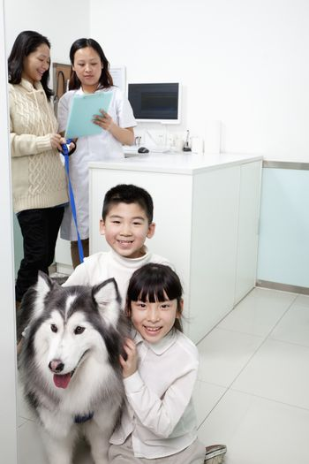 Family with pet dog in veterinarian's office