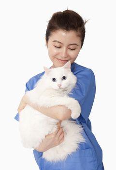 Portrait of female veterinarian holding a white cat