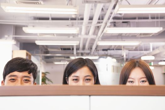 Office workers peeking over divider in office