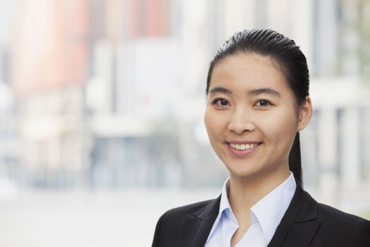 Portrait of smiling young businesswoman, head and shoulders