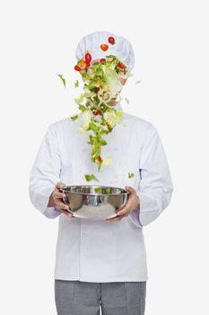 Chef tossing a salad, studio shot