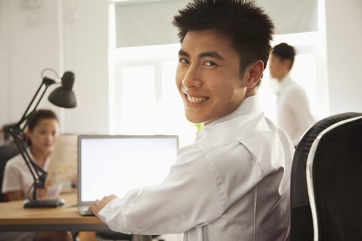 Man working on her laptop and smiling in the office
