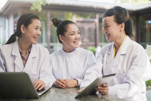 Three Doctors Working in a Courtyard