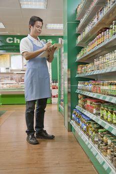 Sales clerk checking merchandise in supermarket