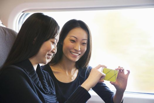 Two Women Looking At Mobile Phone on a Train