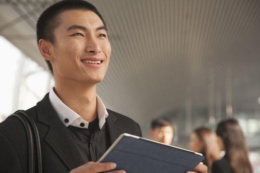 Young Man Using Digital Tablet on Train Platform