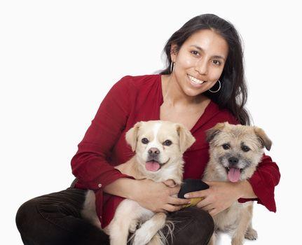 Portrait of woman embracing her dogs, studio shot