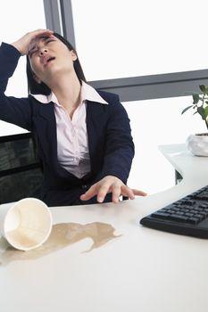 Businesswoman spilling coffee