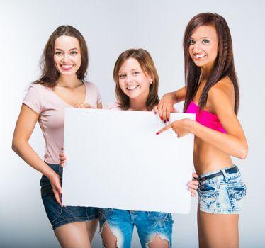 three teenage girls with white banner