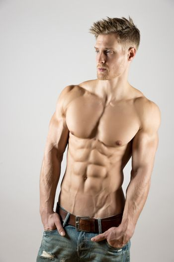 young body art athlete with well trained pecs and abs (pectoral and abdominal muscle) and blue jeans