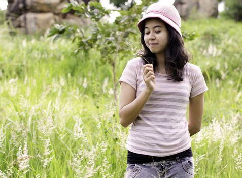 Asian woman outdoors holding flower smiling