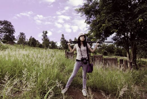 Young photographer carry on tripod in rural field