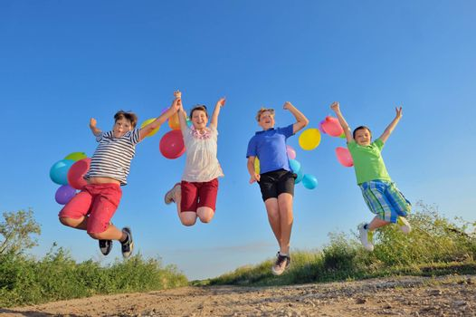 happy children jumping on field with balloons in summer time