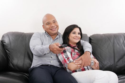 Young couple watching tv on a sofa