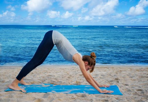 Young pretty woman practicing yoga on the beach by the ocean