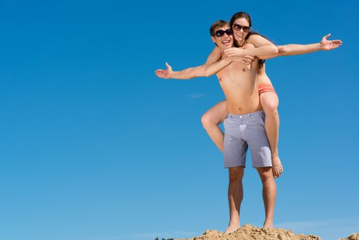 Young couple hugging on a background of blue sky, hold together honeymoon