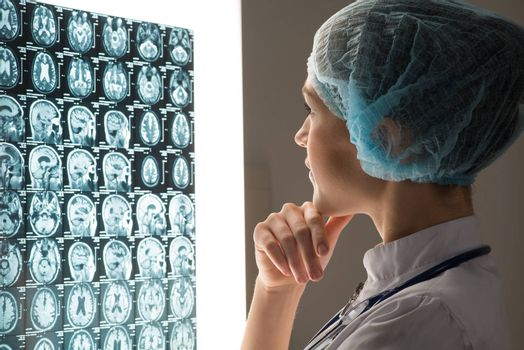 female doctor looking at the x-ray image attached to the glowing screen