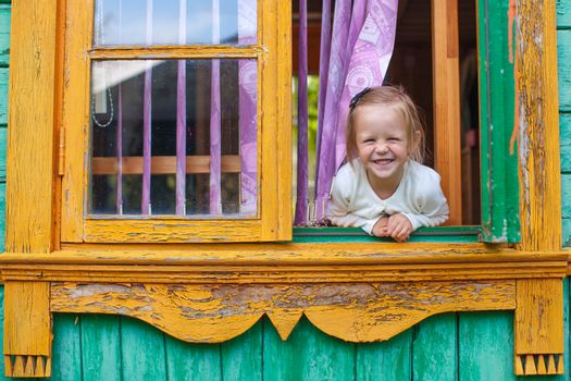 Adorable little girl looks out the window rural house and laughs