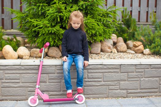Little girl riding a scooter in her yard