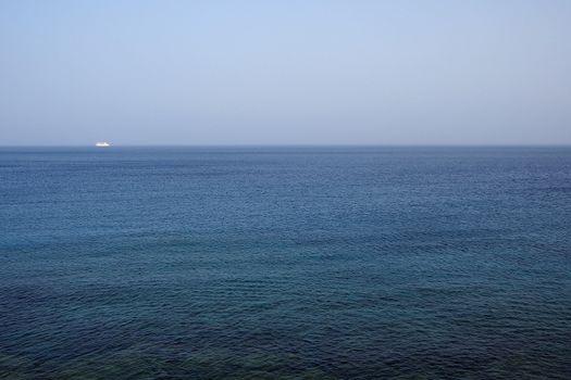 Sailboat sailing far away from coastline