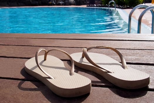 Pair of slippers by a swimming pool