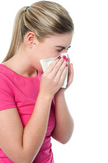 Girl covering her nose with handkerchief while sneezing