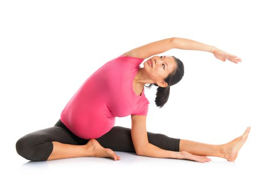 Pregnant woman yoga position seated side stretch.