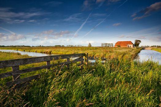 fence and farmhouse in Dutch farmland