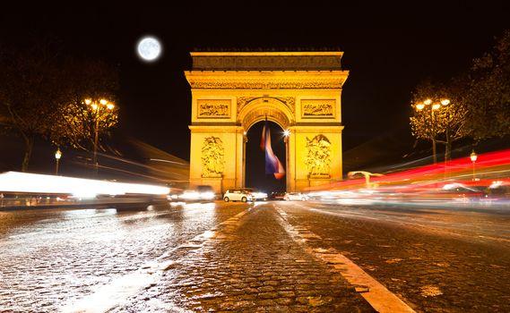 The Arc de Triomphe in Paris illuminated at night.