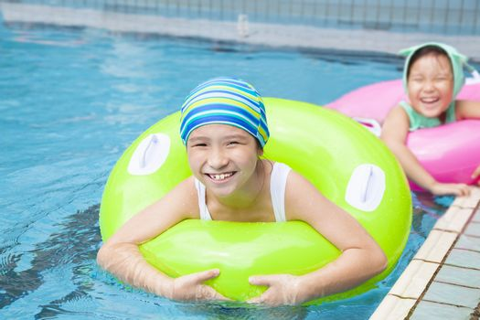 beautiful little girls with inflatable ring at swimming pool