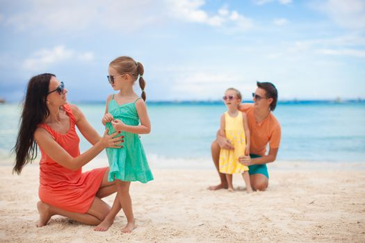 Mom with her older daughter in the foreground and dad with youngest daughter in the background on the beach