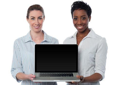 Saleswomen presenting brand new laptop