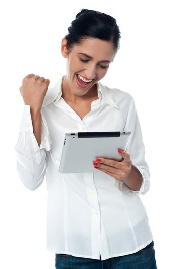 Excited pretty woman using tablet pc