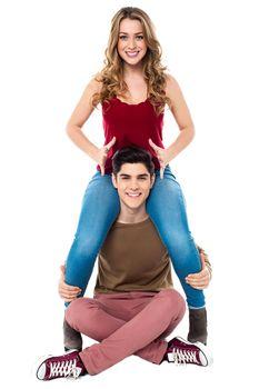 Gorgeous girl sitting on her boyfriend's shoulder