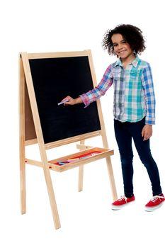 Charming young girl writing on blackboard