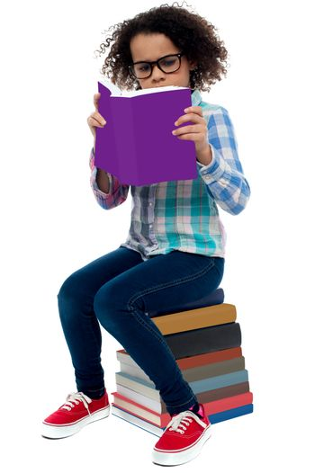 Young kid concentrating while reading a book