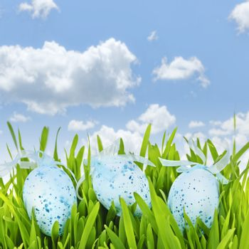 Three blue speckled easter eggs with ribbons in green grass on sky background